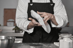 Chef cooking pizza in kitchen Royalty Free Stock Image