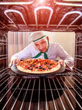 Chef cooking pizza in the oven. royalty free stock photography