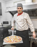 Chef Cooking Pizza. Chef with a pizza on a shovel in a kitchen of a restaurant Stock Image