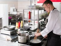 Chef cooking restaurant kitchen professional work. Chef standing in a restaurant kitchen and cooking a meal. A professional at work. Food masterpiece is on its stock photos