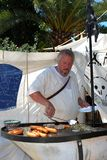 Chef cooking sausages on market stall. Stock Photography