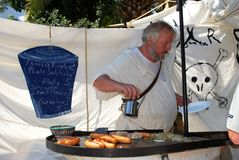 Chef cooking sausages on market stall. Stock Images