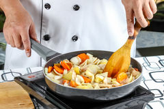 Chef cooking. Stir fry vegetables with pork in outdoor kitchen Stock Image
