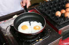 A chef is cooking sunny-side up eggs Stock Image
