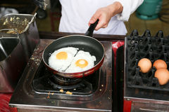 A chef is cooking sunny-side up eggs Royalty Free Stock Image