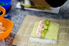 Chef cooking sushi rolls. Chef cooking sushi. Close up photo of some hands making sushi, nori, roll, kitchen, cooking, sushiman, bowls, rice, meshi, shrimps stock images