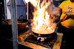 A chef cooking tadka fry in a frying pan at a road side food corner on a stove over flames royalty free stock images