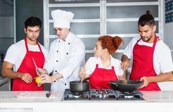Chef cooking with team at kitchen. Of restaurant stock photos