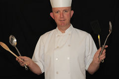 Chef with cooking utensils. Chef in white uniform holding various cooking utensils Royalty Free Stock Photo
