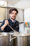 Chef cooking a vegetables stir fry over a hob Stock Image