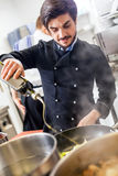 Chef cooking a vegetables stir fry over a hob Stock Photo