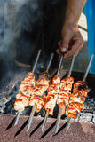 Chef cooks kebabs on grill Royalty Free Stock Photos