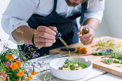 Chef cooks meal. Closeup image of chef cooks delicious meal at luxurious restaurant royalty free stock images