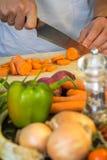 Chef coupant en tranches les carottes fraîches pour une salade Images stock