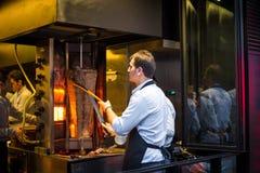 Chef coupant le chiche-kebab turc traditionnel de Doner de nourriture dans le restaur Images libres de droits