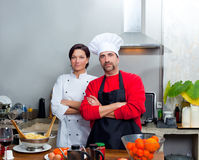 Chef couple man and woman posing in kitchen stock photos