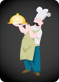 Chef with covered dish. On dark background Royalty Free Stock Photo
