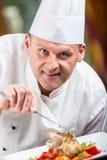 chef Cozinheiro chefe Cooking Cozinheiro chefe que decora o prato Cozinheiro chefe que prepara uma refeição O cozinheiro chefe na fotos de stock