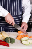 Chef cut carrot. With knife Royalty Free Stock Photo