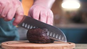 Chef cuts beef into pieces with a sharp knife. Slow motion. Chef cuts beef into pieces with a sharp knife. Slow motion stock video footage