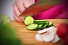 Chef cuts cucumber Stock Photo