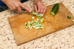 The chef cuts the cucumber on a wooden  Board. Stock Photo