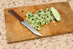 The chef cuts the cucumber on a wooden  Board. Royalty Free Stock Photography