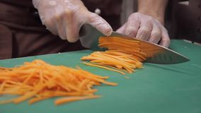 Chef cuts fresh carrot on green cutting board in industrial kitchen. Male cook in brown apron holding sharp knife, cut thin slices on little long pieces in stock video