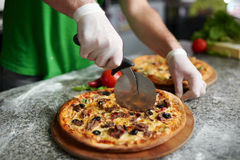 Chef cuts freshly prepared pizza on a wooden substrate. Stock Image