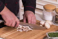 The chef cuts the mushrooms Royalty Free Stock Photos
