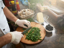 Chef cuts the parsley on  board for pizza Stock Photography