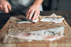 Chef cuts raw fish slices on wooden cutting board Stock Photography