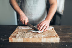 Chef cuts raw fish slices on wooden cutting board Royalty Free Stock Photography
