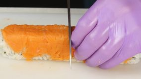 Chef cuts the ready roll in half. Close up stock video