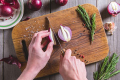 Chef cuts red onion on brown cutting board. Stock Photos