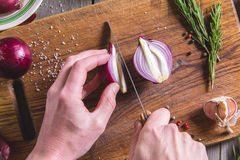 Chef cuts red onion on brown cutting board. Stock Photography