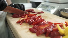 Chef cuts red pepper on cutting board in industrial kitchen. Hot-tasting powder prepared from dried and ground peppercorns, commonly used as spice condiment stock video footage