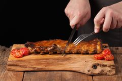 The chef cuts it with a sharp knife ready to eat pork ribs, lying on an old wooden table. A man prepares a snack to beer on a blac. K background with copy space Stock Photos