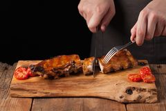 The chef cuts it with a sharp knife ready to eat pork ribs, lying on an old wooden table. A man prepares a snack to beer on a blac. K background with copy space Royalty Free Stock Photo