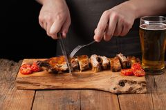 The chef cuts it with a sharp knife ready to eat pork ribs, lying on an old wooden table. A man prepares a snack to beer on a blac. K background with copy space Stock Photo