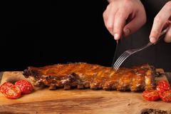 The chef cuts it with a sharp knife ready to eat pork ribs, lying on an old wooden table. A man prepares a snack to beer. On a black background with copy space Royalty Free Stock Image