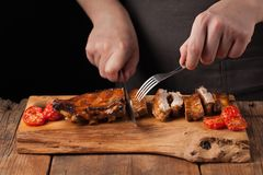 The chef cuts it with a sharp knife ready to eat pork ribs, lying on an old wooden table. A man prepares a snack to beer. On a black background with copy space Royalty Free Stock Photography