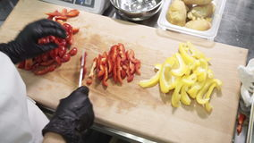 Chef cuts strips red bell peppers on table in industrial kitchen. stock video