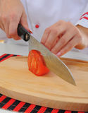 Chef cuts the tomato Stock Photo