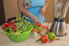 Chef cuts the vegetables into a meal. Preparing dishes. A woman uses a knife and cooks. Woman`s hands cooking healthy meal in the Royalty Free Stock Photography