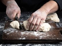 Chef cuts white wheat flour dough into pieces royalty free stock photos
