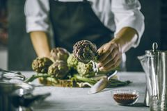 Chef cutting artichokes for dinner preparation - Man cooking inside restaurant kitchen royalty free stock image