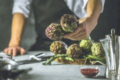 Chef cutting artichokes for dinner preparation - Man cooking inside restaurant kitchen stock image