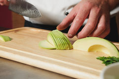 Chef cutting avocado on table Royalty Free Stock Images
