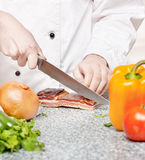 Chef cutting bacon Stock Photography